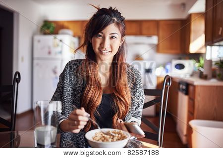 cute asian teen girl eating breakfast in kitchen with smart phone
