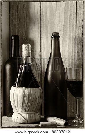 A wine still life with warm light from a window on the side. Three bottles, a wine glass and cork screw in a rustic setting, Vertical format. Vintage effect added.