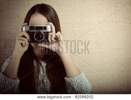 Photographer woman holding retro camera and taking photos, toned