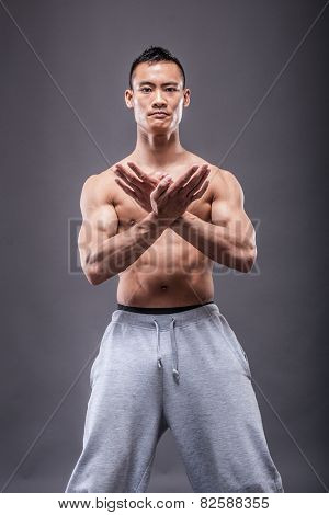 Young asian man workout over grey background