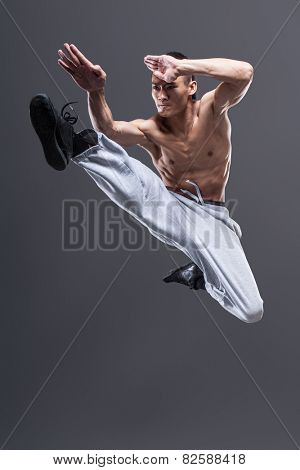 Young asian man workout over grey background karate jump kick