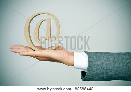 closeup of the hand of a young businessman showing an at sign