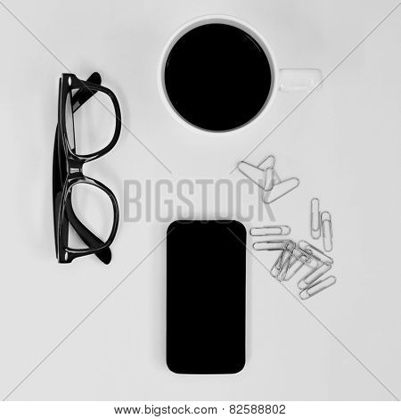 high-angle shot of a pair of eyeglasses, a smartphone, a cup of coffee and some paperclips on a white table