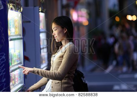 Japan vending machines - Tokyo woman buying drinks. Young student or female tourist choosing a snack or drink at vending machine at night in famous Harajuku district in Shibuya, Tokyo, Japan.