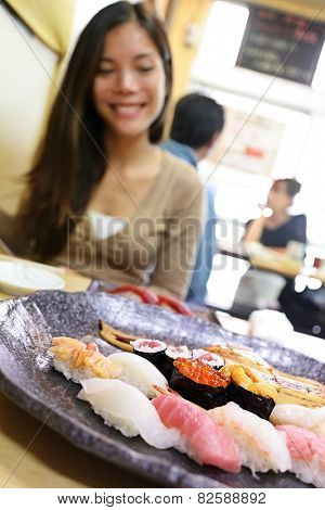 Sushi eating woman tourist in Tokyo restaurant. Travel destination famous Tsukiji Fish Market, person looking at plate of raw seafood presented as sashimi. Japanese food.