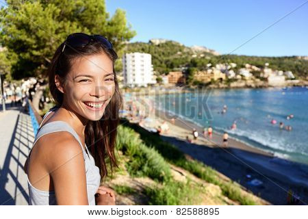 Tourist woman on beach summer vacation in Mallorca (Majorca). Asian lady smiling at camera in Sant Elm (San Telmo) in Andratx, Balearic Islands, Mediterranean sea, Spain, Europe.