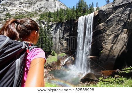 Hiker girl looking at Vernal Fall, Yosemite, USA. Nature landscape of waterfall in Yosemite National Park, California, USA with unrecognizable woman hiking overlooking view.