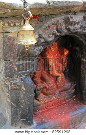 KATHMANDU, NEPAL - APRIL 2014 : A brass bell in front of a Ganesha Hindu shrine in Kathmandu, Nepal on 12 April 2014. Devotees ring the bell to drive away evil spirits.