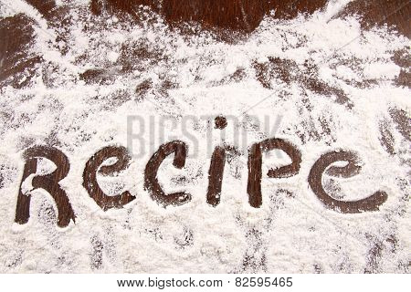 Word recipe written in white flour on a wooden table