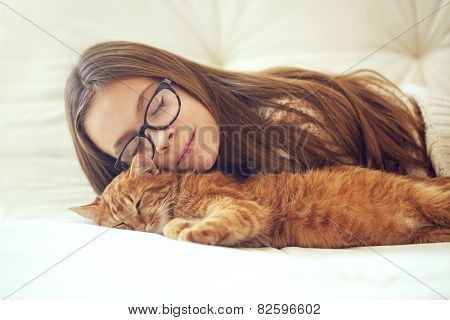 Cute ginger cat sleeps near kid girl on the sofa