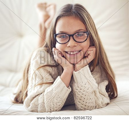 Home portrait of 8 years old school girl wearing glasses resting on the sofa, looking at camera