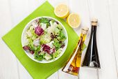 foto of condiment  - Fresh healthy salad and condiments over white wooden table - JPG