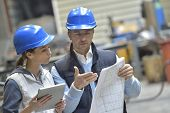 stock photo of mechanical engineering  - Engineers in mechanical factory reading instructions - JPG