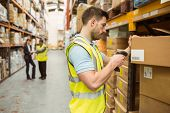 stock photo of barcode  - Warehouse worker scanning barcode on box in a large warehouse - JPG