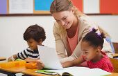 pic of classmates  - Pretty teacher helping pupil in classroom at the elementary school - JPG