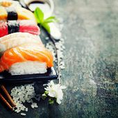 pic of chopsticks  - sushi with chopsticks on old  wooden background - JPG