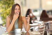 picture of restaurant  - Tired woman yawning while is working on the phone at breakfast in a restaurant - JPG