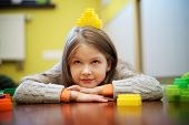 stock photo of daycare  - Happy beautiful girl plays with blocks at home - JPG