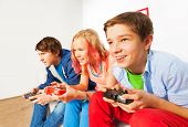 picture of indoor games  - Three friends with joysticks playing game console sitting on the sofa at home - JPG