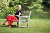 image of sitting a bench  - Single blonde woman sitting on the wooden bench into the nature - JPG