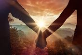 picture of lovers  - Couple holding hands rear view against sunrise over mountains - JPG