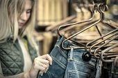 image of boutique  - Beautiful blonde female looking jeans in the boutique - JPG