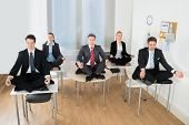 pic of crossed legs  - Meditating Businesspeople Sitting On Desk With Their Legs Crossed In Office - JPG