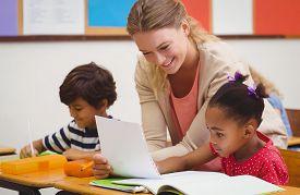 foto of child development  - Pretty teacher helping pupil in classroom at the elementary school - JPG