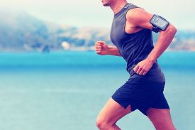 image of cardio exercise  - Cardio runner running listening smartphone music - JPG