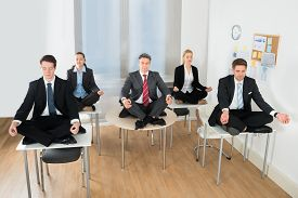 stock photo of crossed legs  - Meditating Businesspeople Sitting On Desk With Their Legs Crossed In Office - JPG