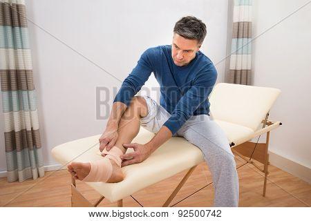 Man Tying Bandage To His Foot