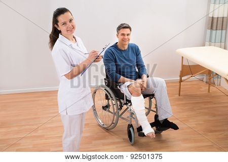Doctor With Patient Writing On Clipboard