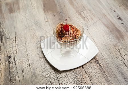 Ice Cream With Chocolate Crumb And Cherry In Glass Bowl