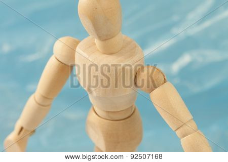 Wooden human scale model figure standing on water background