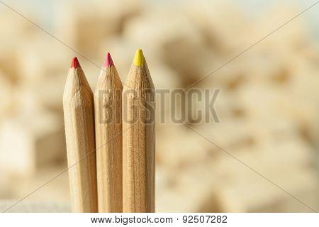 Three wooden color pencils on de-focused background