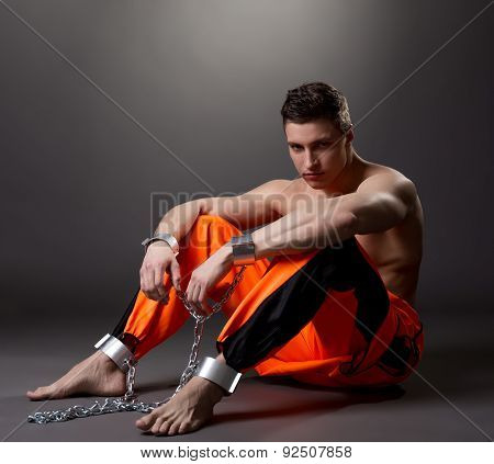 Handsome male model posing as prisoner in studio