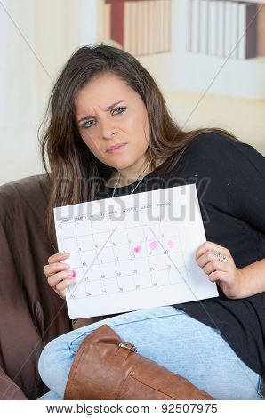 brunette girl sitting in sofa holding up a calendar