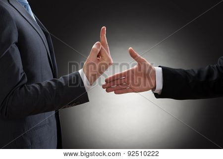 Person Showing Fuck Sign To Businessman Offering Handshake
