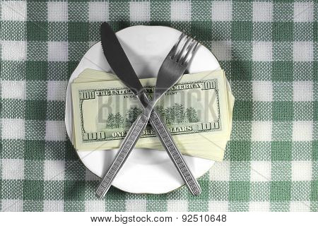 Stack Of Dollar Bills, Knife And Fork Lying On A Silver Platter With A Golden Platter On A Checkered
