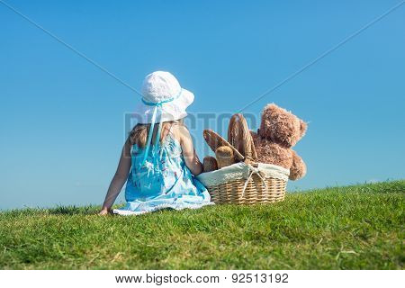 Girl On Green Grass With Teddy Bear In Basket