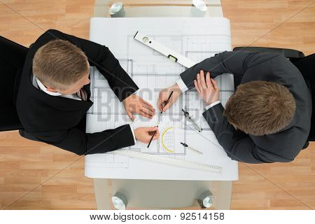 Two Businessman Drawing Plan On Blueprint