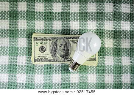 Led Light Bulb Lying On The Stack Of Dollars