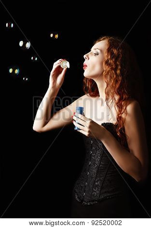 Beautiful Redhead Girl Blows Bubbles. Studio Portrait, Profile View