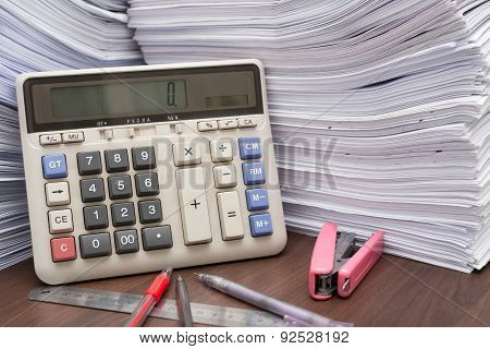 Pile Of Documents On Desk Stack Up High With Calculator Pen And Ruler On Office Desk