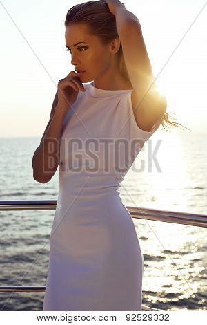 Beautiful Girl With Blond Hair In Elegant Dress Posing On Yacht