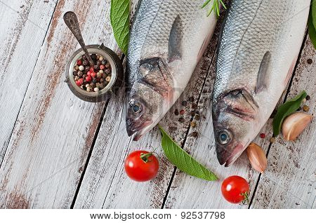 Two raw seabass with spices on an old wooden background.