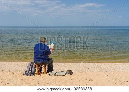 Senior man reading book sitting on a beach