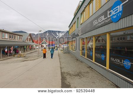 Tourists walk by the street of Longyearbyen, Norway.