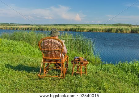 Senior man reading book sitting in the wicker rocking-chair