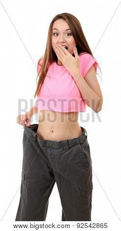 Young slim woman wearing too big pats isolated on white